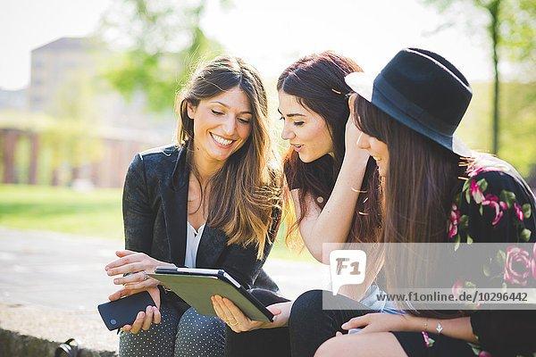 Drei junge Freundinnen teilen sich das Update auf dem digitalen Tablett im Park