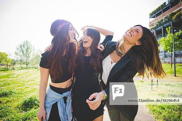 Drei junge Freundinnen  die zusammen im Park lachen.