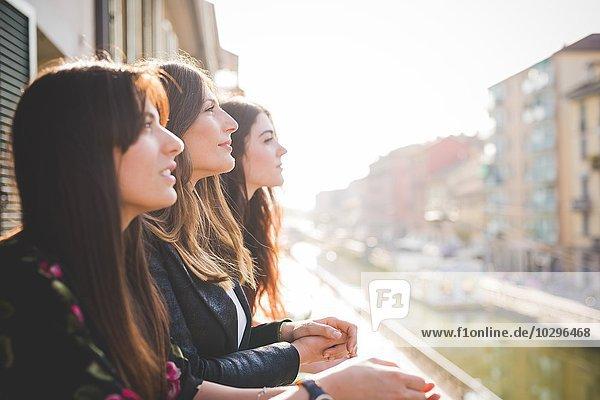 Drei junge weibliche freunde blickte vom wasser balkon