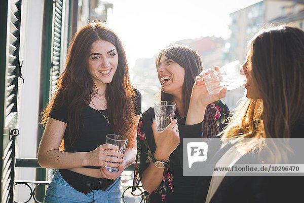 Drei junge Freundinnen beim Lachen und Plaudern auf dem Balkon am Wasser