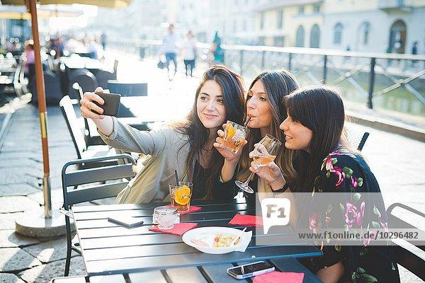 Drei junge Frauen posieren für Smartphone Selfie am Waterfront Café
