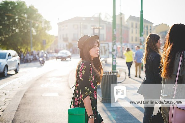 Junge Frau  die hinter Freunden in der Stadt spazieren geht