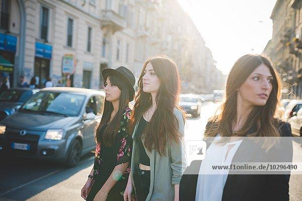 Drei junge Frauen schlendern durch die Stadt