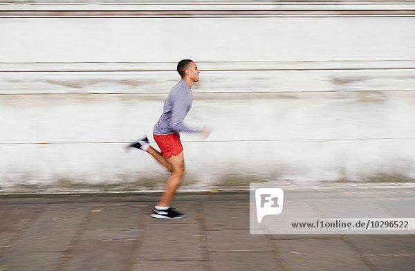 Männlicher Läufer  der auf dem Bürgersteig rast