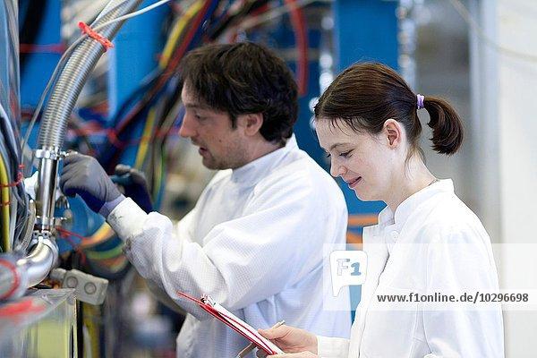 Seitenansicht der männlichen und weiblichen Kollegen im Laborkittel  mit Zwischenablage