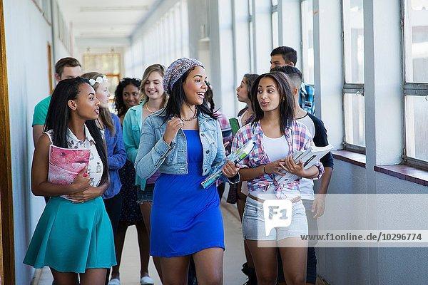 Students walking down hallway  chatting