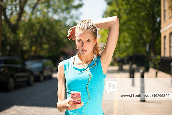 Läufer hört Musik im Smartphone auf der Straße  Wapping  London