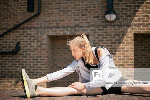 Läufer streckt sich auf dem Gehweg  Wapping  London