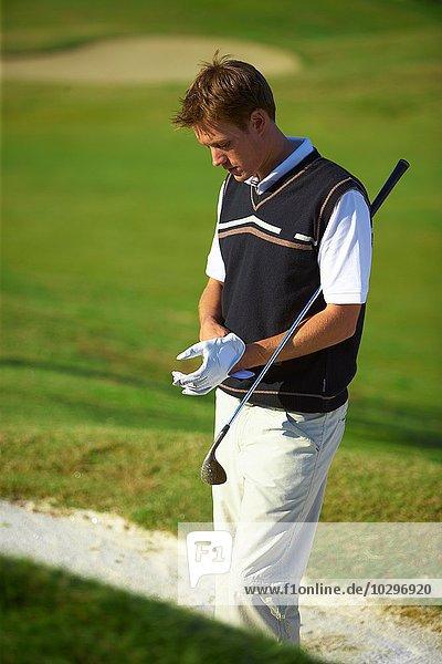 Golfer mit Golfhandschuh mit Golfschläger unter dem Arm  Blick nach unten