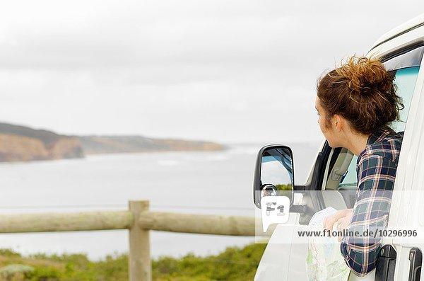 Junge Frau schaut aus dem Fenster des Wohnmobils  Point Addis  Anglesea  Victoria  Australien