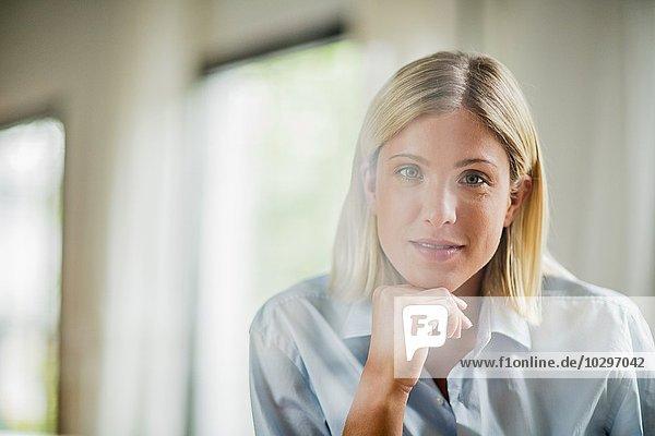 Porträt einer schönen jungen Frau mit Kinn an der Hand
