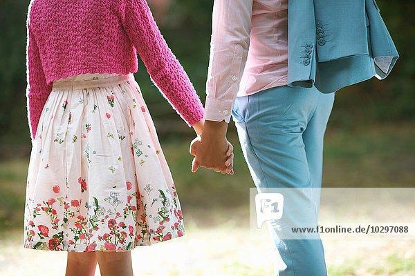 Ausschnitt eines Mädchens und eines Jungen  die im Garten Händchen halten.