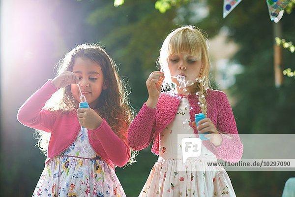 Zwei süße Mädchen blasen Blasen im Garten