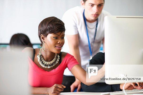 Schüler  die im Klassenzimmer am Desktop-Computer arbeiten