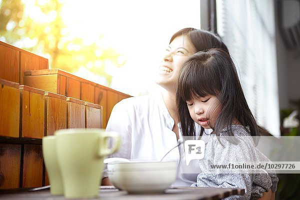 Chinesische Mutter und kleine Tochter beim gemeinsamen Frühstück auf dem Balkon im Sonnenschein