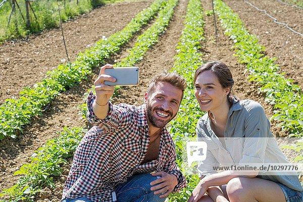 Junges Paar im Gemüsegarten geduckt mit dem Smartphone  um Selfie zu nehmen.