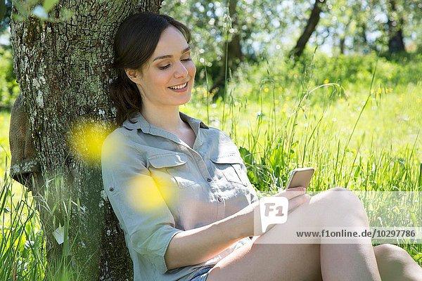 Junge Frau lehnt sich mit dem Smartphone an den Baum und schaut lächelnd nach unten. Junge Frau lehnt sich mit dem Smartphone an den Baum und schaut lächelnd nach unten.