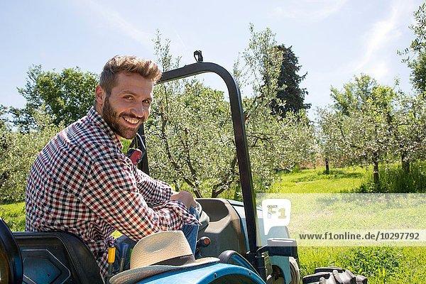Junger Mann sitzt im Traktor und schaut über die Schulter  lächelnd auf die Kamera. Junger Mann sitzt im Traktor und schaut über die Schulter, lächelnd auf die Kamera.