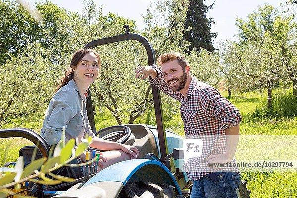 Junges Paar mit Traktor sieht lächelnd in die Kamera Junges Paar mit Traktor sieht lächelnd in die Kamera