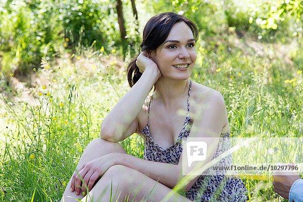Junge Frau sitzt auf Gras und schaut lächelnd weg. Junge Frau sitzt auf Gras und schaut lächelnd weg.