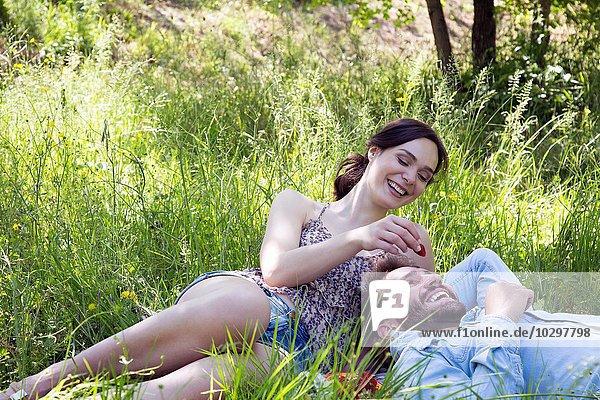 Junges Paar liegt auf Gras und isst Erdbeeren lächelnd Junges Paar liegt auf Gras und isst Erdbeeren lächelnd