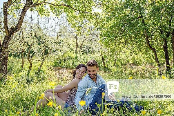 Junges Paar sitzt Rücken an Rücken auf Gras und schaut lächelnd nach unten. Junges Paar sitzt Rücken an Rücken auf Gras und schaut lächelnd nach unten.