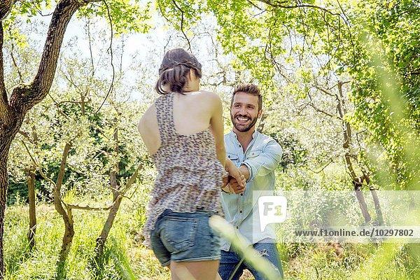 Junges Paar  das im Wald Händchen hält und lächelnd herumalbert.