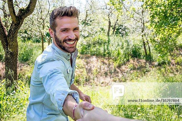 Junger Mann hält die Hand und schaut lächelnd in die Kamera. Junger Mann hält die Hand und schaut lächelnd in die Kamera.