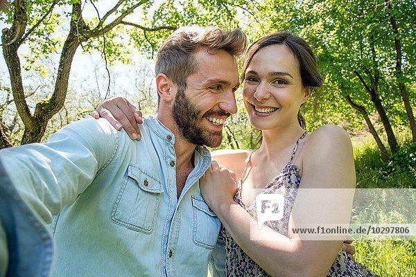 Junge Frau mit Arm um den jungen Mann  der lächelnd in die Kamera schaut. Junge Frau mit Arm um den jungen Mann, der lächelnd in die Kamera schaut.