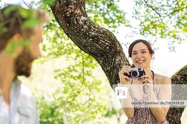 Junge Frau unter dem Baum fotografiert jungen Mann Junge Frau unter dem Baum fotografiert jungen Mann