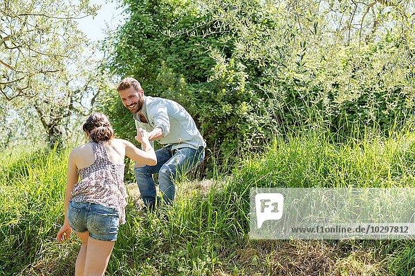 Tiefblick auf einen jungen Mann  der einer jungen Frau den Berg hinauf hilft. Tiefblick auf einen jungen Mann, der einer jungen Frau den Berg hinauf hilft.