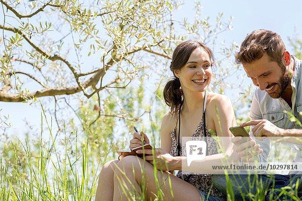 Niedriger Blickwinkel auf ein junges Paar  das auf ein lächelndes Smartphone blickt. Niedriger Blickwinkel auf ein junges Paar, das auf ein lächelndes Smartphone blickt.