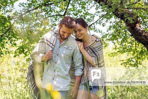Junges Paar in Decke gehüllt und lächelnd nach unten schauend Junges Paar in Decke gehüllt und lächelnd nach unten schauend