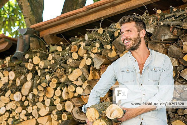 Junger Mann hält gehacktes Brennholz und schaut lächelnd weg. Junger Mann hält gehacktes Brennholz und schaut lächelnd weg.