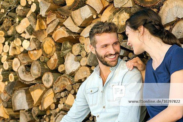 Junges Paar sitzt vor gehacktem Holz und lächelt. Junges Paar sitzt vor gehacktem Holz und lächelt.