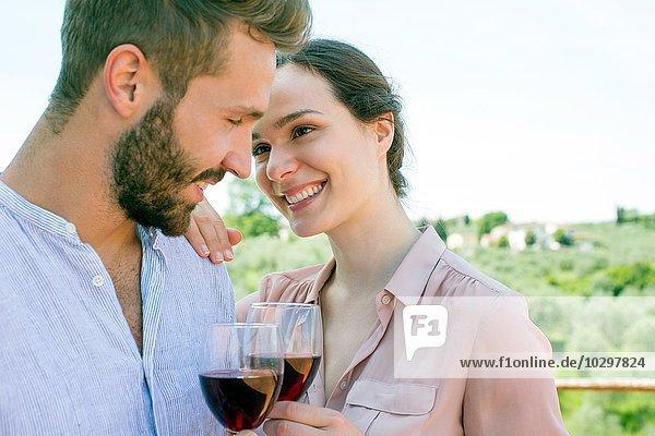 Junges Paar hält Weingläser von Angesicht zu Angesicht lächelnd Junges Paar hält Weingläser von Angesicht zu Angesicht lächelnd