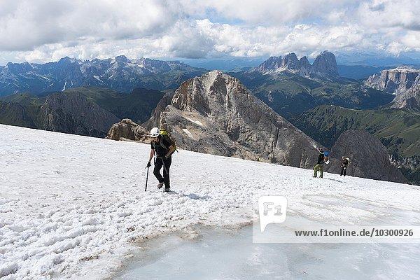 Bergsteiger überqueren Schneefeld am Gipfel Punta Penia  Marmolata  hinten die Langkofelgruppe  Dolomitan  Alpen  Trentino-Alto Adige  Südtirol  Italien  Europa