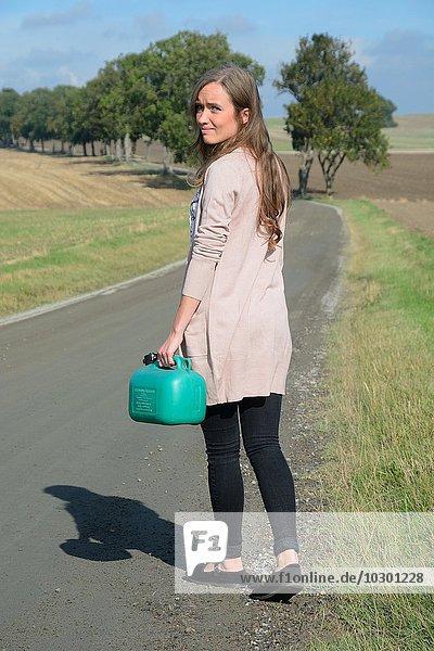 Junge brünette Frau mit Benzinkanister unterwegs auf einer Landstraße  Krageholm  Skåne län  Südschweden  Schweden  Europa