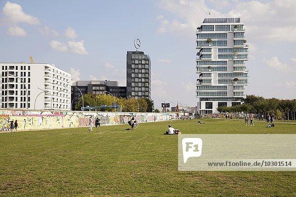 Menschen im ehemaligen Todesstreifen an der East Side Gallery  neues Luxus-Appartementhaus hinten  Berlin  Deutschland  Europa