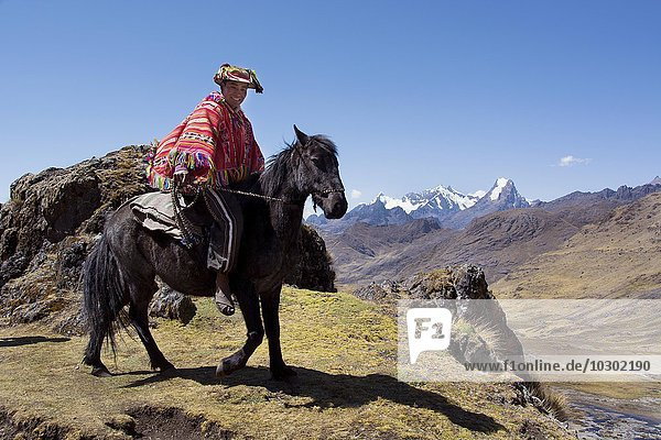 Indio mountain guide with colorful poncho riding on horseback  in the mountains  Andes  Cusco Province  Peru  South America