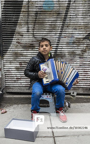A boy playing the accordion on the road  Istanbul  Turkey  Asia