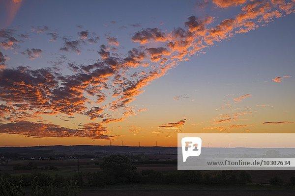 Rot angestrahlte Wolken bei Sonnenuntergang  rötlicher Abendhimmel  Windräder am Hoizont  Haßberge  Unterfranken  Bayer  Deutschland  Europa