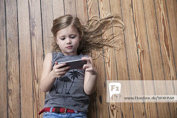 Kleines Mädchen auf dem Boden liegend mit Smartphone