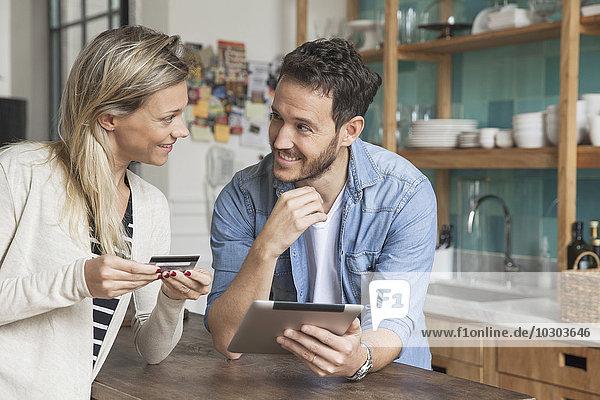 Paar mit digitalem Tablett zum Online-Shopping zu Hause