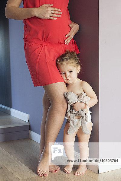 Kleines Mädchen klammert sich an das Bein ihrer schwangeren Mutter mit beunruhigendem Gesichtsausdruck.