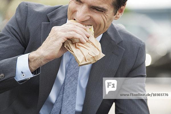 Geschäftsmann beim Sandwichessen unterwegs