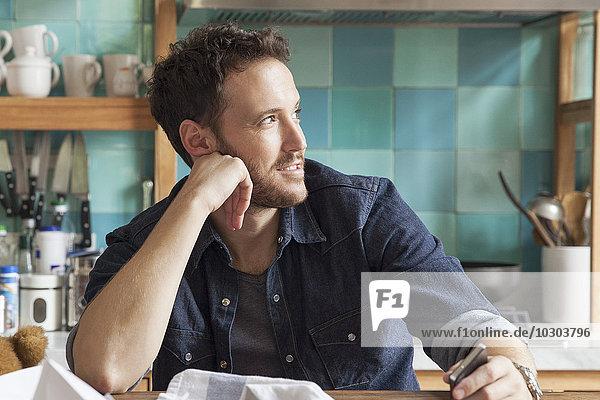 Mann träumt in unordentlicher Küche