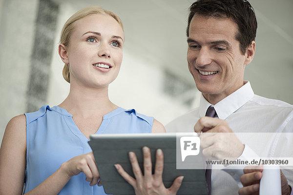 Geschäftsleute  die gemeinsam auf das digitale Tablett schauen und lachen