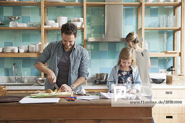 Kleine Tochter beim Zeichnen und Kochen  während die Eltern das Essen zubereiten.