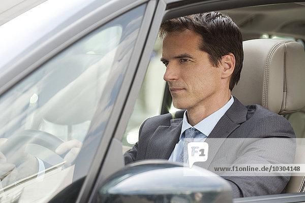 Geschäftsmann beim Autofahren
